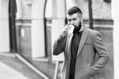 Time to drink. Bearded man drinking morning coffee. Hipster with disposable paper cup walking in city. Businessman in. Hipster style holding takeaway coffee stock images