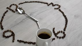 Time to drink coffee. The watch dial of coffee beans is laid out on a wooden table. a cup of coffee instead of 7 o`clock and spoon. S instead watch arrows stock footage