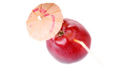 Time to drink fresh apple juice. Red fresh apple with umbrella and cocktail tube Stock Image