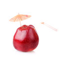 Time to drink fresh apple juice. Red apple with cocktail tube and umbrella Stock Photography