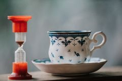 Elegant tea cup and hourglass stand shelf. Time to drink tea. A neat cup for tea with a blue pattern and a saucer stand on wooden rails. Near the hourglass Royalty Free Stock Images