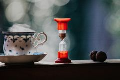 Elegant tea cup and hourglass stand shelf. Time to drink tea. A neat cup for tea with a blue pattern and a saucer stand on wooden rails. Near the hourglass Stock Photography