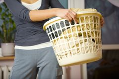 Time to drying clothes. Woman standing and holding in hands full laundry basket. Closeup on basket. Front view royalty free stock images