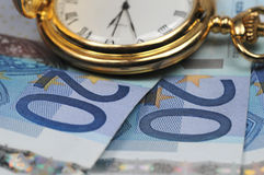 Time to earn some money. An old fashioned watch lying on some twenty Euro notes royalty free stock photo