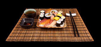 Time to Eat. Collection of sushi on a plate of rice set out on a bamboo mat with tea, sauce and chopsticks Royalty Free Stock Photography