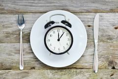 Time to eat with clock plate fork and knife on a table Stock Images