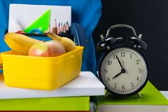 Time to eat from the yellow container, between lessons, background with a banana and an apple royalty free stock image