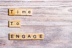 Time to engage text on cubes on wooden background.  Royalty Free Stock Image