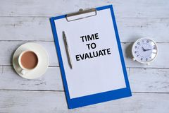 Time to evaluate written on a clipboard. Top view of clipboard with paper written `TIME TO EVALUATE` with pen,table clock and a cup of coffee on white wooden Royalty Free Stock Image