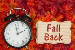 It is time to fall back message Daylight Savings. Daylight Savings Time message, Some fall leaves and retro alarm clock with text Fall Back on wood frame stock photo