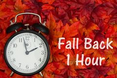 It is time to fall back message Daylight Savings. Daylight Savings Time message, Some fall leaves and retro alarm clock with text Fall Back 1 Hour royalty free stock photo
