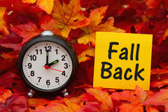 It is time to fall back message. Daylight Savings Time message, Some fall leaves and retro alarm clock with text Fall Back Stock Photo