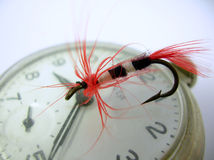 Time to fo fishing. Hand tied fly atop an antique pocket watch Royalty Free Stock Photos