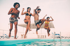 Time to get refreshed. Group of beautiful young people looking happy while jumping into the swimming pool together Stock Photography