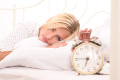Time to get up for displeased blonde lady. Displeased blonde woman with alarm clock in light bedroom Royalty Free Stock Photo