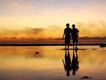 Time to go home kids. Two children going home after playing in the water when the sun sets Stock Image