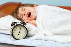 The time to go to school. The small boy awake by an alarm clock ring Royalty Free Stock Images