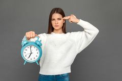 Time to go to school. Young girl standing isolated on grey with clock showing gun gesture royalty free stock image