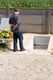 Time to grieve. Boy in front of open grave stock image