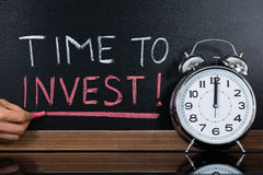 Time To Invest Concept Written On Blackboard. Stopwatch In Front Of Time To Invest Concept Written On Blackboard Stock Images