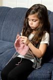 Time to knit. A little girl learning to knit while sitting on the couch Stock Photography