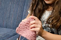Time to knit. A little girl learning to knit while sitting on the couch Royalty Free Stock Photography