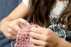 Time to knit. A little girl learning to knit while sitting on the couch Stock Photos