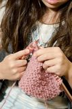 Time to knit. A little girl learning to knit while sitting on the couch Stock Photo