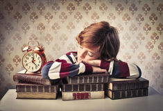 Time to learn. Child sleeping on some books beside an alarm clock Stock Image