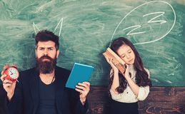 Time to learn concept. Teacher devil and sleepy girl. Bearded man with alarm clock and book. Little child student tired. Time to learn concept. Teacher devil and stock photo