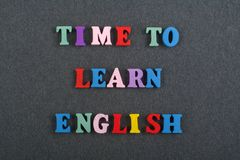 TIME TO LEARN ENGLISH word on black board background composed from colorful abc alphabet block wooden letters, copy stock photography