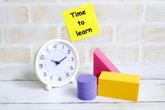 Time to learn. Selective focus of yellow sticky notes written with & x27;TIME TO LEARN& x27; with colorful soft building blocks and table clock. Education theme Stock Images