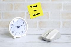 Time to learn. Selective focus of yellow sticky notes written with & x27;TIME TO LEARN& x27; with computer mouse and table clock. Education theme Royalty Free Stock Image