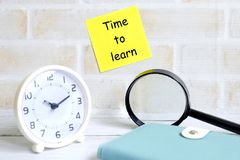 Time to learn. Selective focus of yellow sticky notes written with & x27;TIME TO LEARN& x27; with magnifying glass,notebook and table clock. Education theme Stock Photos