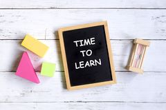 Time to learn. Top view of hourglass,colorful soft block,and blackboard written with & x27;TIME TO LEARN& x27; on white wooden background Stock Image