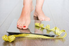 Time to lose kilograms with woman feet stepping on a weight scale. Warped in yellow measuring tape. Eating disorder concept with different conceptions on royalty free stock photo