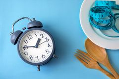 Time to lose weight , eating control or time to diet concept , a. Larm clock with healthy tool concept decoration on blue background royalty free stock image
