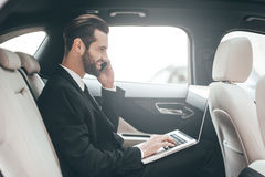 Time to make decision. Confident young businessman working on his laptop and talking on the phone while sitting in the car Royalty Free Stock Photos