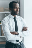 Time to make decision. Handsome young African man keeping arms crossed and looking somewhere while standing in creative office Royalty Free Stock Photo