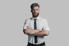 Time to make decision. Handsome young man keeping arms crossed and looking at camera while being in front of grey background Royalty Free Stock Images
