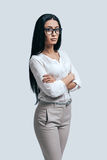 Time to make important decision. Confident young woman in a white shirt and glasses keeping arms crossed while standing against grey background Stock Image