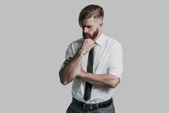 Time to make important decision. Thoughtful young businessman keeping hand on chin while standing against grey background Royalty Free Stock Photos