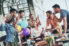 Time to make a wish. Group of happy people celebrating birthday among friends and smiling while having a dinner party stock photo