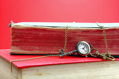 Time to open your mind and learn new things. Golden key with a clock over old books Royalty Free Stock Photo