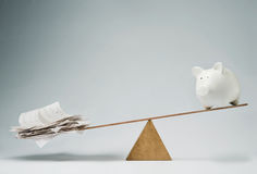 Time to pay the bills. Piggy bank balancing on seesaw over a stack of bills Stock Photography