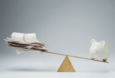 Time to pay the bills. Piggy bank balancing on seesaw over a stack of bills Royalty Free Stock Images