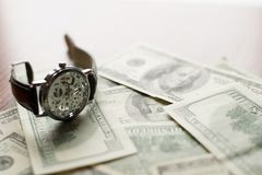 Time to pay - 100 dollars banknote and classic watch with Roman numerals royalty free stock photos