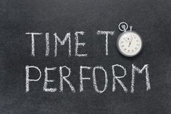 Time to perform. Phrase handwritten on chalkboard with vintage precise stopwatch used instead of O Stock Photos