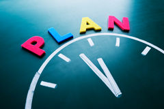 Time to plan concept. Color word and clock on blackboard Royalty Free Stock Photo