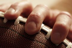 Time To Play Football. Fingers on an American Football ready to make a pass royalty free stock image